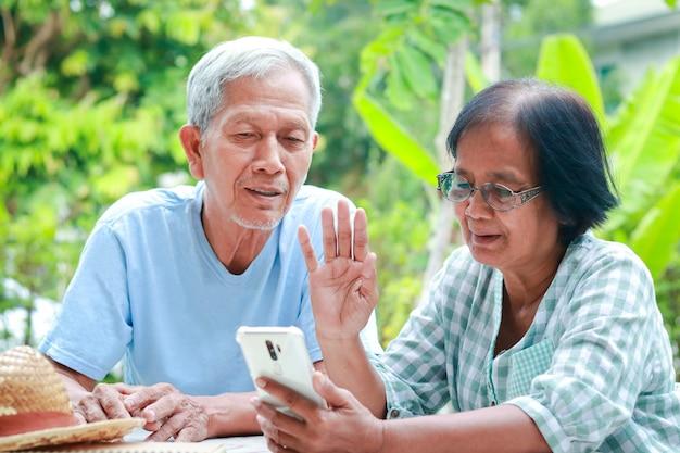 Aziatisch bejaarde echtpaar dat gelukkig thuis woont zittend in de tuin met een smartphone, online chattend met uw kind. familieconcept, gezondheidszorg voor ouderen in de pensioengerechtigde leeftijd