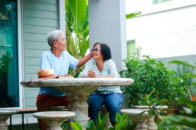 Aziatisch bejaarde echtpaar dat gelukkig thuis woont, zittend in de tuin voor het huis lachen, praten, plezier hebben. concept van familie gezondheidszorg voor ouderen met pensioen.