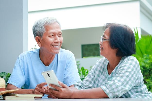 Aziatisch bejaarde echtpaar gelukkig thuis wonen zittend in de tuin met een smartphone. familieconcept, gezondheidszorg voor ouderen in de pensioengerechtigde leeftijd.