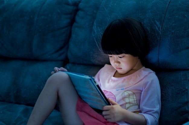 Aziatisch chinees meisje speelt smartphone, kijkt naar smartphone, kind gebruikt telefoon en speelt spel, kind gebruikt mobiel, verslaafd spel en cartoon