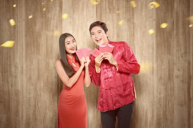 Aziatisch chinees paar dat in cheongsamkleding rode enveloppen houdt