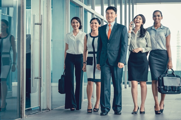 Aziatisch commercieel team van stafmedewerkers die bureau lopen