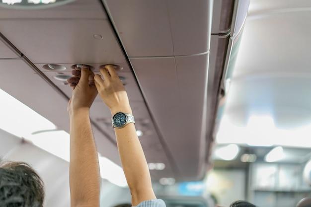 Aziatisch de cabinepersoneel van paarmensen, hand omhoog om consolepaneel aan te passen; de airconditioning, licht / lamp boven de goedkope vliegtuigstoel.
