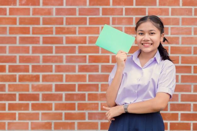 Aziatisch de student eenvormig gelukkig lachend portret van de meisjestiener met boek voor onderwijs terug naar schoolconcept.