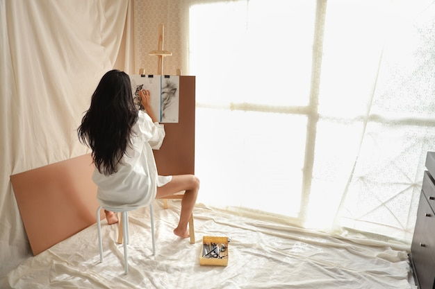 Aziatisch de tekeningsbeeld van de kunstenaarsvrouw met potlood in woonkamer