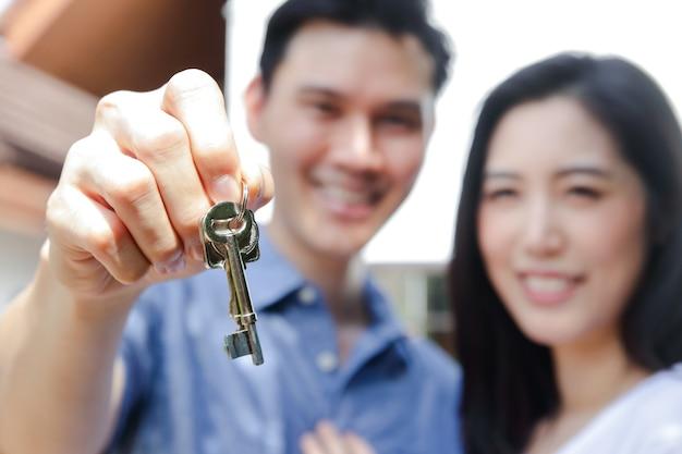 Aziatisch echtpaar houdt de sleutels van het nieuwe huis. het concept van het starten van een gelukkig gezin