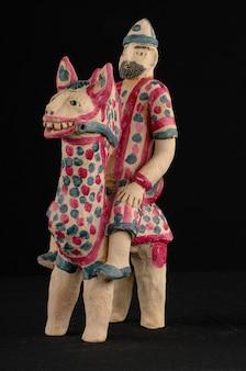 Aziatisch en oosters beschilderd speelgoed van verbrande klei in de vorm van een man op een paard op een zwarte achtergrond