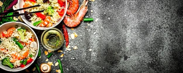 Aziatisch eten. chinese noedels met groenten en garnalen. op een oude rustieke achtergrond.