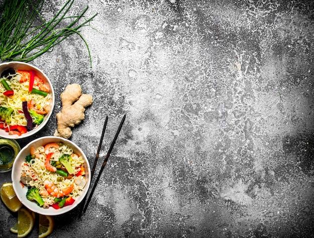Aziatisch eten. chinese noedels met groenten. op rustieke achtergrond.