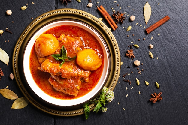 Aziatisch eten concept zelfgemaakte pittige kip masala of thaise massaman curry met kruiden voorgrond op zwarte leisteen steen met kopie ruimte