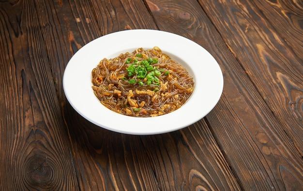 Aziatisch eten. gebakken glazen кice-noedels met vlees en groenten. chinese vermicelli van de glasrijst die met vlees en tomaten wordt gebakken. koreaanse funchoza cellofaannoedels