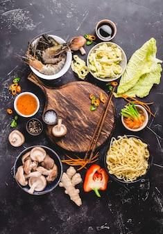 Aziatisch eten koken concept. leeg houten bord, noedels, groenten roerbak, garnalen, sauzen, eetstokjes.