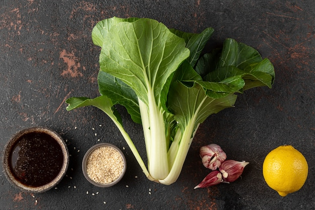 Aziatisch eten koken concept. vers geoogste biologische paksoi chinese kool met ingrediënten op zwarte achtergrond