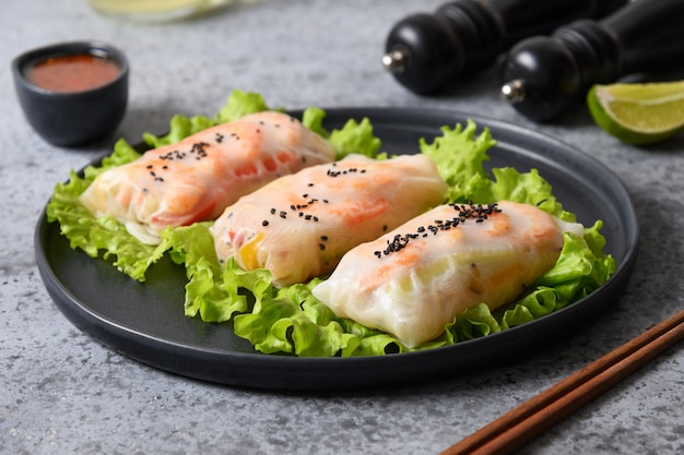 Aziatisch eten loempia's met garnalen, groenten verpakt in rijstpapier op grijze achtergrond. detailopname. vietnamese keuken.