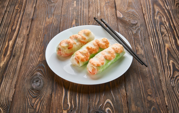 Aziatisch eten loempia's met garnalen op een donkere houten achtergrond. loempia's in rijstpapier met stokjes. ruimte voor tekst