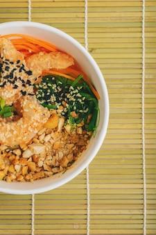 Aziatisch eten met spicy garnalen por bowl met rijst, zeewier en sesamzaadjes, avocado met stokjes op de bamboe mat over de grijze stenen achtergrond met kopie ruimte. gezonde lunchbox met zeevruchten.