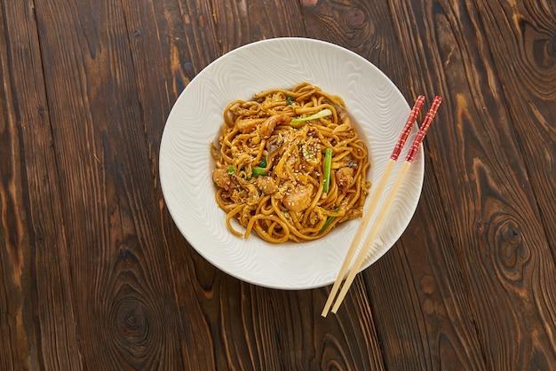 Aziatisch eten, roergebakken noedels met groenten, sesamzaadjes op houten tafel met stokjes, bovenaanzicht en kopie ruimte voor menu-ontwerp