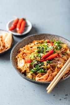 Aziatisch eten, woknoedels en groenten in keramische kom, selectieve aandacht