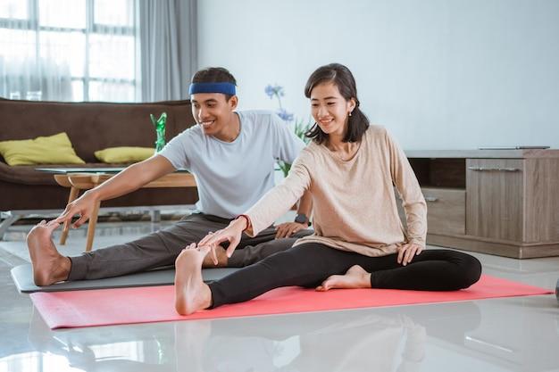 Aziatisch geschiktheidspaar, man en vrouw die samen thuis uitoefenen die yoga in woonkamer doen