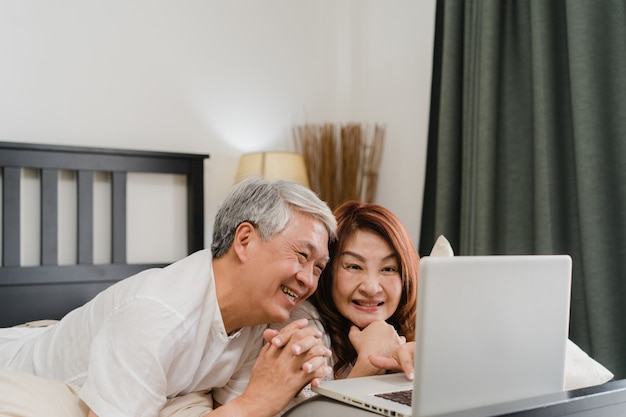Aziatisch hoger paar dat laptop thuis met behulp van. aziatische hogere chinese grootouders, echtgenoot en vrouw gelukkig na kielzog omhoog, lettend op film liggend op bed in slaapkamer thuis in het ochtendconcept.