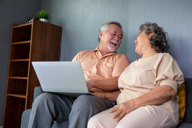 Aziatisch hoger paar die in videogesprekpraatje op laptop computer, slimme technologie voor ouderdom en online activisme spreken die verbonden concept blijven
