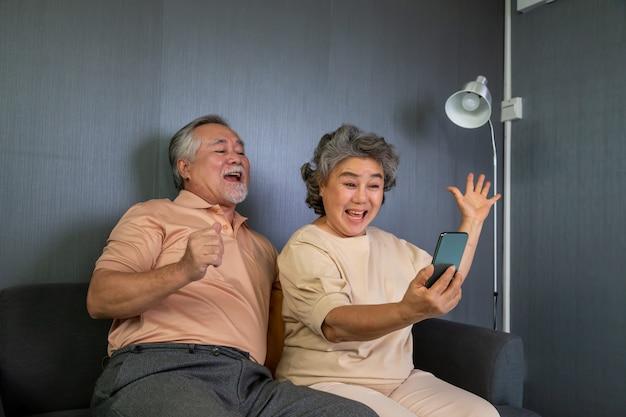 Aziatisch hoger paar die in videogesprekpraatje spreken op mobiele telefoon, slimme technologie voor ouderdom en online activisme die verbonden concept blijven