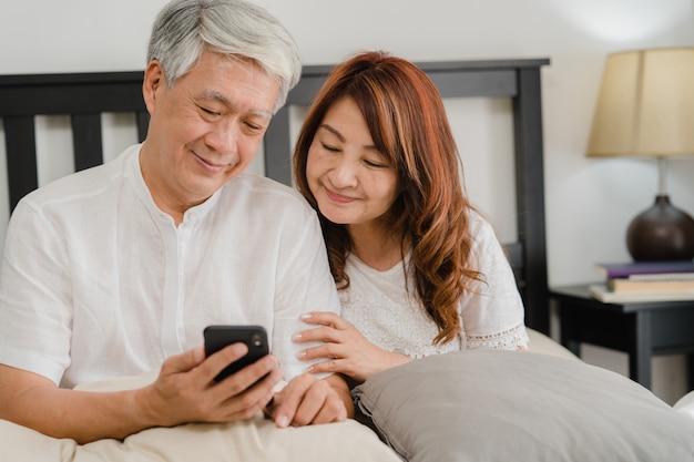 Aziatisch hoger paar die mobiele telefoon thuis met behulp van. aziatische hogere chinese grootouders, echtgenoot en vrouw gelukkig na kielzog omhoog, lettend op film liggend op bed in slaapkamer thuis in het ochtendconcept.