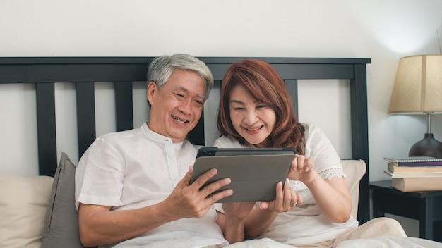 Aziatisch hoger paar die tablet thuis gebruiken. aziatische hogere chinese grootouders, echtgenoot en vrouw gelukkig na kielzog omhoog, lettend op film liggend op bed in slaapkamer thuis in het ochtendconcept.