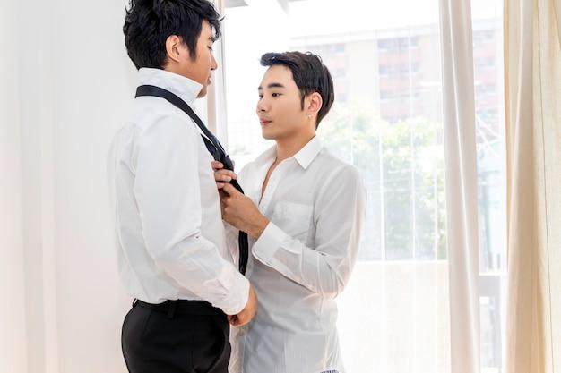 Aziatisch homoseksueel paar dat elkaar helpt aankleden. concept lgbt-homo.