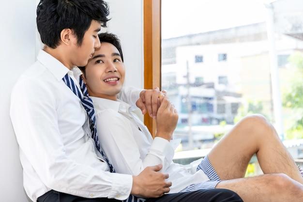 Aziatisch homoseksueel paar gelukkig en thuis ontspannend in woonkamer