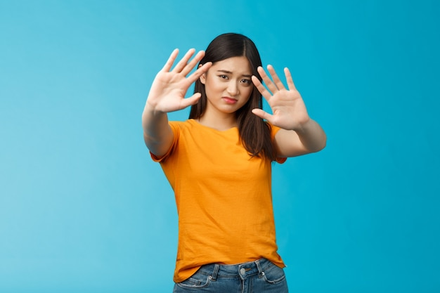 Aziatisch humeurig ontevreden dwaas timide meisje dat vraagt om het licht uit te doen, haar niet te fotograferen, de handen op te heffen, het gezicht te bedekken, een stap terug te doen en teleurgesteld ineen te krimpen, een blauwe achtergrond overstuur onwillig. ruimte kopiëren