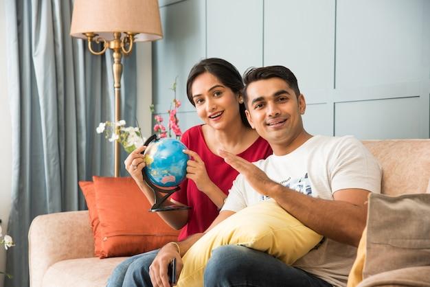 Aziatisch indisch jong stel dat een vakantiereis plant met 3d globe-model terwijl ze op de bank of bank zitten