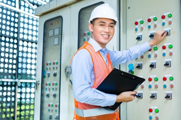 Aziatisch-indonesische technicus of elektricien maakt functietest op paneel of schakelkast voor de besturing van airconditioners op de bouwplaats of in de fabriek voor acceptatie