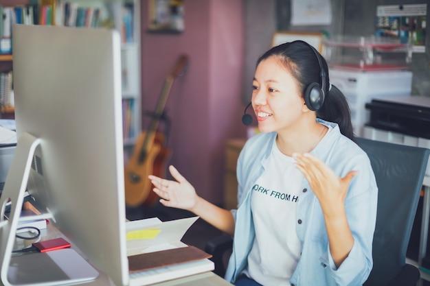 Aziatisch jong bedrijfsvrouwenvideogesprek van huisbureau.