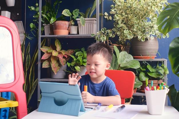 Aziatisch jong geitje die de computer die van tabletpc met behulp van zijn online les thuis bestuderen
