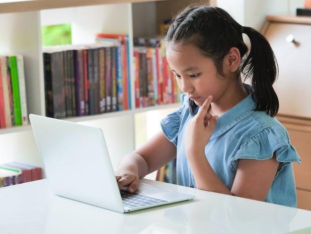 Aziatisch jong geitje die laptop in bibliotheekruimte met behulp van.