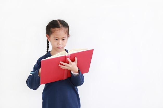 Aziatisch jong geitjemeisje die in toevallige schooluniform open boek houden dat over witte achtergrond in studioschot wordt geïsoleerd.