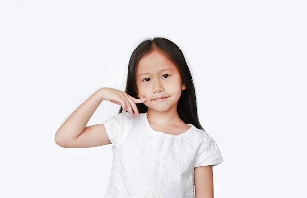 Aziatisch jong geitjemeisje die vinger op wang houden