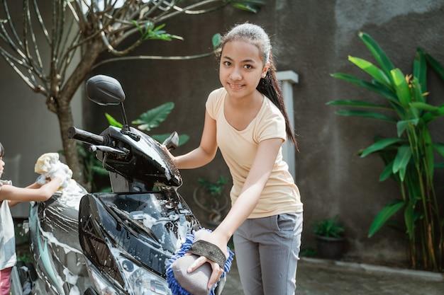 Aziatisch jong meisje dat een motorfiets wast