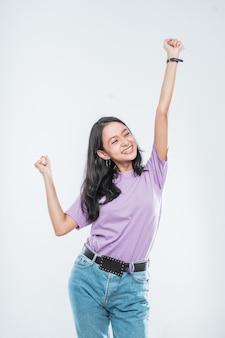 Aziatisch jong meisje dat gelukkig glimlacht terwijl gebalde in vuisten en twee geïsoleerde handen ophief