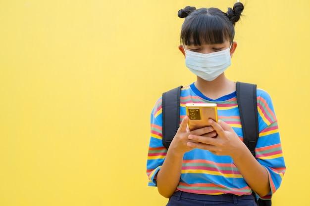 Aziatisch jong meisje draag masker gebruik mobiele telefoon op gele achtergrond.