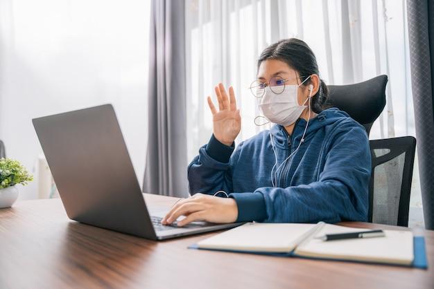 Aziatisch jong meisje draagt een maskergebaar van het begroeten van student die thuis online leert met een koptelefoon en laptop