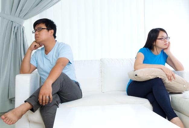 Aziatisch jong paar dat argument in de woonkamer heeft