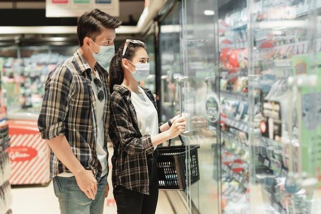 Aziatisch jong stel in beschermingsmasker staat om te kiezen voor het winkelen van diepvriesproducten tijdens een uitbraak van het coronavirus