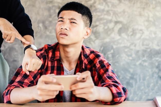 Aziatisch jongens speelspel dat zijn boze moeder negeert