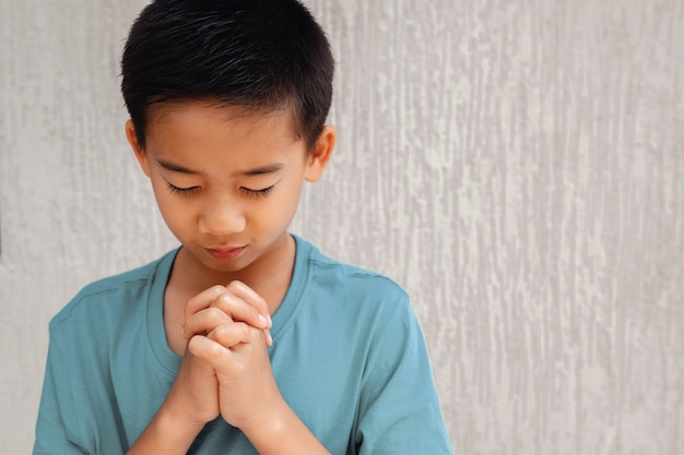 Aziatisch jongenskind die met gesloten ogen bidden, het concept van het christendomgeloof