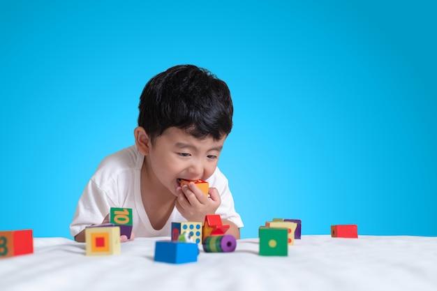 Aziatisch jongensspel vierkante blok puzzel speelgoed op het bed