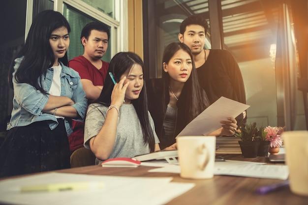 Aziatisch jonger freelance team concentreert zich op werkproject op computermonitor