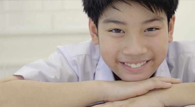 Aziatisch kind dat camera met glimlachgezicht bekijkt