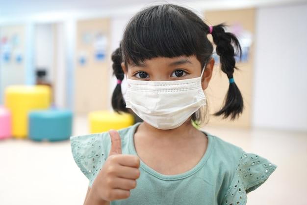 Aziatisch kind gebruikt een medisch masker of een chirurgisch masker om haar te beschermen tegen virussen, ziekte, covid-19 en coronavirus-infectie.